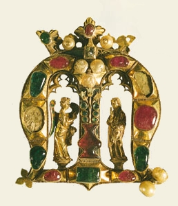 Gothic Founder's Jewel. A gold crowned M adorned with rubies, emeralds, pearls, enamelling and gothic details in the archs that serve as shrine spaces for the Angel of Annunciation and the Virgin Mary.