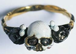 Gold and black enamel Mourning Ring from the Museum of London, features central skull in white on a gold band with black enamal to either side and in the skull orifices.