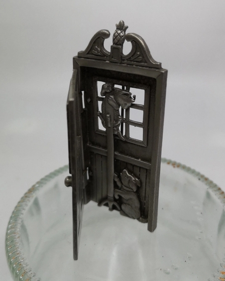 A pewter brooch with open door with, cat on an coat rack and a dog at the base.